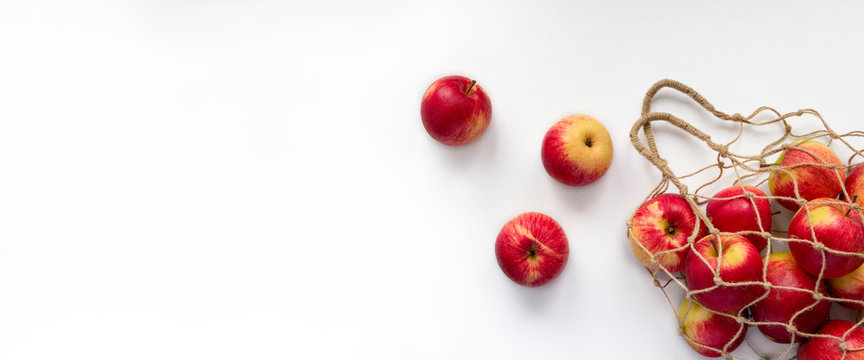 Fresh red apples in string bag on white background. Eco mesh with colorful fruits. Banner with copy space, top view, flat lay. Ecology and healthy eating concept