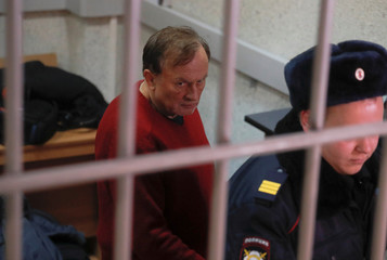 Russian historian Sokolov is escorted inside a court building in Saint Petersburg