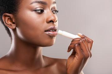Fototapete - Black millennial girl applying hygienic balm on lips