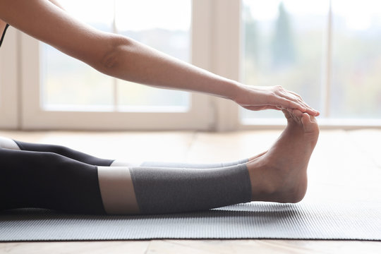 Legs of woman making pilates on wooden floor