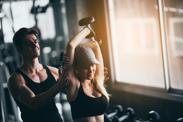 Athletic fitness woman pumping up muscles with dumbbells, Fit woman working out with trainer at the gym