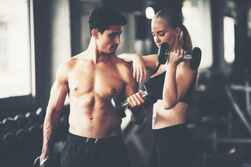 Fitness couple - woman and man in sport gym