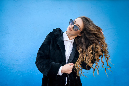 Stylish young woman in fur coat on blue wall background. Beauty and fashion.