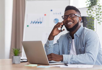 Happy black businessman talking on phone, receiving good news