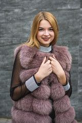 Stylish woman in fur coat posing outdoors on city street. Fashion concept
