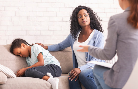 Black mom comforting her little daughter at psychologist consultation