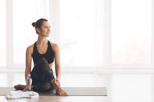 Slim woman resting on mat after training
