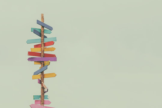 Retro styled image of colorful wooden direction arrow signs