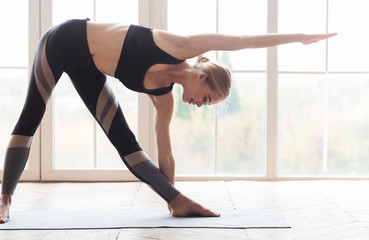 Active young woman making triangle yoga pose at studio