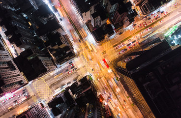Car, taxi, and bus traffic on road intersection at night in Hong Kong downtown district, drone aerial top view. Street commuter, Asia city life, or public transportation concept Wall mural