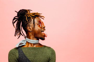 Fun studio profile portrait of trendy young man with sunglasses and  tongue out.