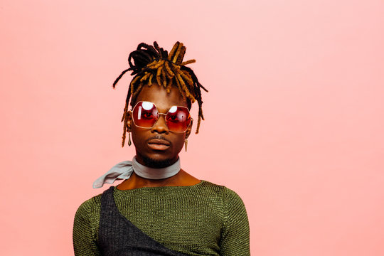 Portrait of a serious young man in green with dreadlocks and red sunglasses, isolated on pink