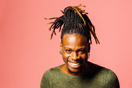 Portrait of a happy, smiling  young man in with cool dreadlocks hairstyle looking at camera, isolated on pink.