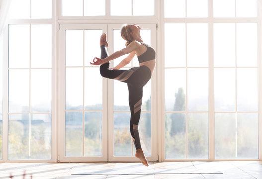 Beautiful young flexible woman exercising at studio