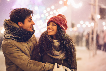 Couple Hugging Standing On A Street Decorated With Winter Lights