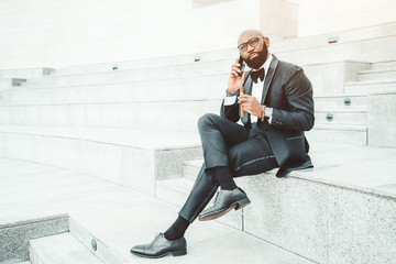 An elegant bald Afro man in a black formal suit and spectacles, with a beard and holding a cigar in his hand, is sitting outdoors on the marble seat of an amphitheater and having a phone conversation