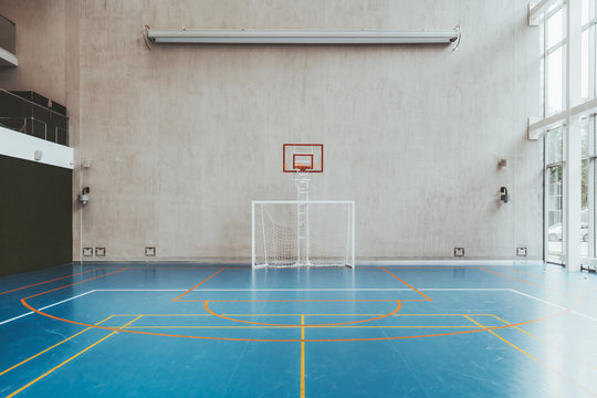 Front view of the court in the gymnasium hall; an indoor modern office stadium with a basketball basket and hoop, football goal, blue floor, a concrete wall with an undeployed projection screen above