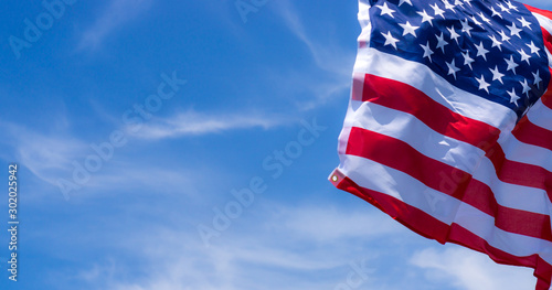 US American flag on blue sky background. For USA Memorial day, Veterans day, Labor day, or 4th of July celebration. Top view, copy space for text.