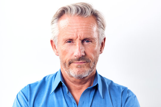 Studio Shot Of Mature Man With Serious Expression Against White Background At Camera