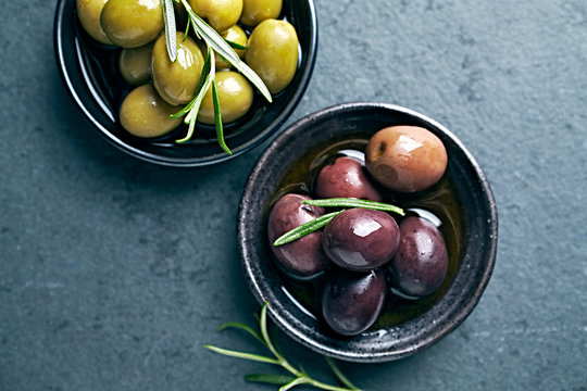 Whole green and black olives in olive oil. Flat lay. Copy space. Mediterranean cuisine