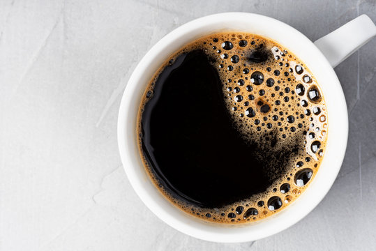 Fragrant fresh black espresso with coffee foam in a white cup. View from above. Black coffee drink close-up.