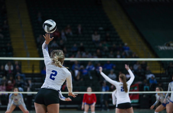 A young woman serves during a volleyball tournament