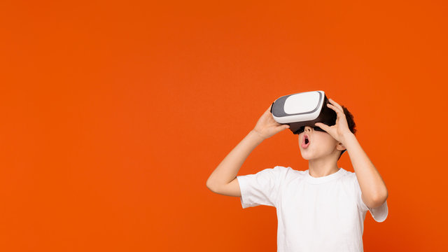 Amazed teen boy experiencing virtual reality in headset