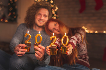 Couple celebrating New Year holding cupcakes with candles 2020