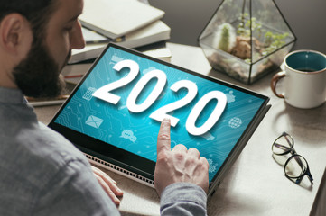 Man selected 2020 on his tablet pc. New 2020 year in modern technologies.