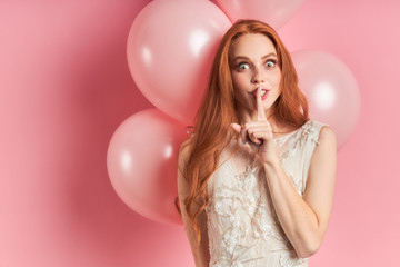 Attractive surprised woman with auburn hair stand in coquettish gesture. Pink air balloons behind.Pink isolated background