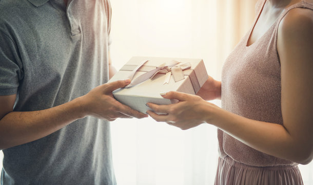 Lovely asia couple holding gift box surprise