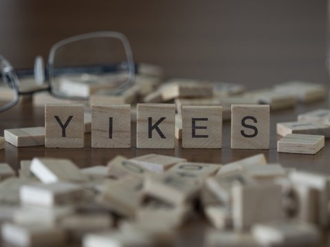 The concept of yikes represented by wooden letter tiles