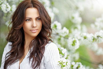 Beautiful woman in blooming garden in spring - close up portrait