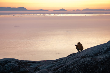 Photographer silhouette shooting sea outdoors at sunset background in arctic city of Ilulissat Greenland