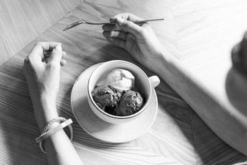 woman with ice cream at a table in a cafe, black and white photo