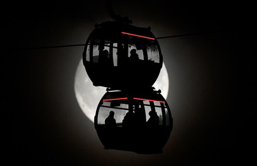 Passengers are seen silhouetted by the moon as they ride on the Emirates Air Line cable car over the River Thames in London, Britain