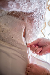 wedding dress , buttons fastens the bride's mother. rear view