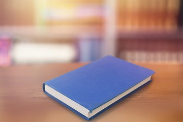Wall Mural - A blue book on a wooden table in the library