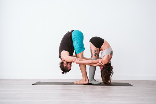 young couple Couple practicing acro yoga in white studio or gym. Healthy lifestyle