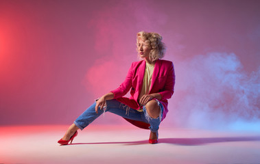 Slim tanned woman dressed in stylish clothes, and red heels, sitting on squat, looking away, showing dancing element on studio background, jazz funk street hip hop music