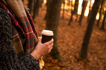 Woman holding coffee to go cup with cozy scarf outdoor in fall season