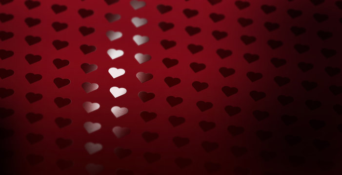 A heart pattern of spot uv varnish print on red note paper background.