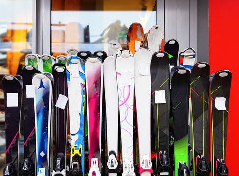 Several multicolored skiing at rental point.