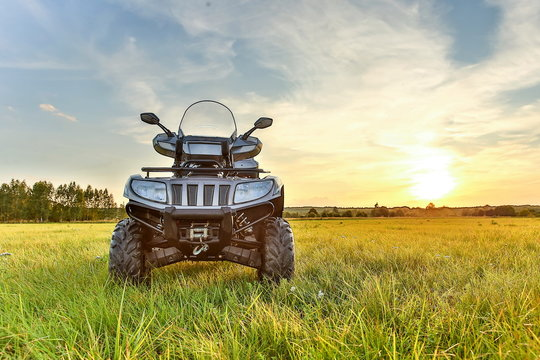 gray ATV on grass in summer at sunset with copy space. beautiful quad bike at sunset in summer front side view