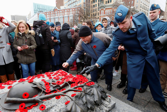 Canadians place poppies on the Tomb of the Unknown Soldier at the National War Memorial on Remembrance Day in Ottawa