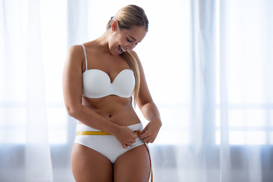 Happy young woman because she has lost weight measuring her body at home.
