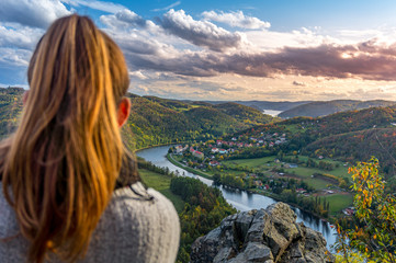 Beautiful girl enjoying life and watching the river, mountains and hills during sunset on the viewpoint (Zduchovice, Solenice, Altán view, hidden gem among travel destinations in Czech republic)