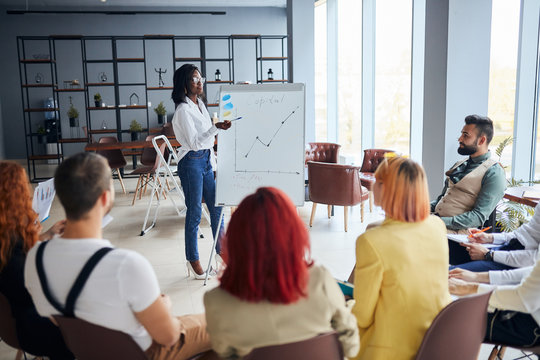 black businesswoman stand talking explaining making flip chart presentation for office employees using diagrams, motivated african American speaker coach present business plan