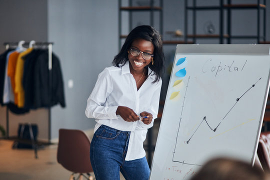 Positive african business lady in white shirt and blue jeans stand talking explaining making flip chart presentation for younger leaders, share business experience with smile