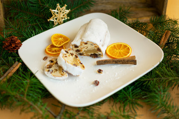 Bratapfel-Stollen auf weißem Teller zwischen Weihnachtlichen Dekorationen